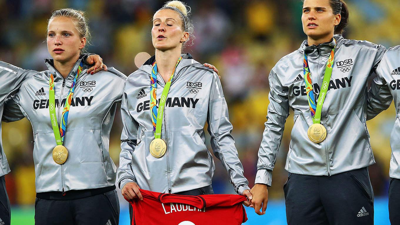 Anjà Mittag et Marozsan Dzsenifer tenant le maillot de Simone Laudher, blessée, lors de la remis de la médaille d'Or aux JO de Rio 2016. Crédit dfb. Lesfeminines.fr